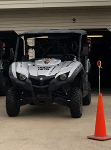 """A UTV with """"Turtle Patrol"""" on the front sits near a garage."""