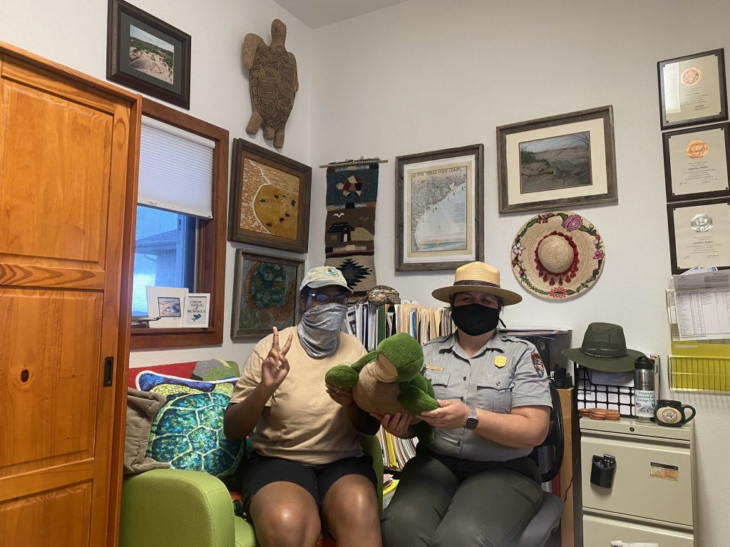 Amani Canada and Cynthia Rubio hold a sea turtle stuffed animal in Rubio's decorated office space.