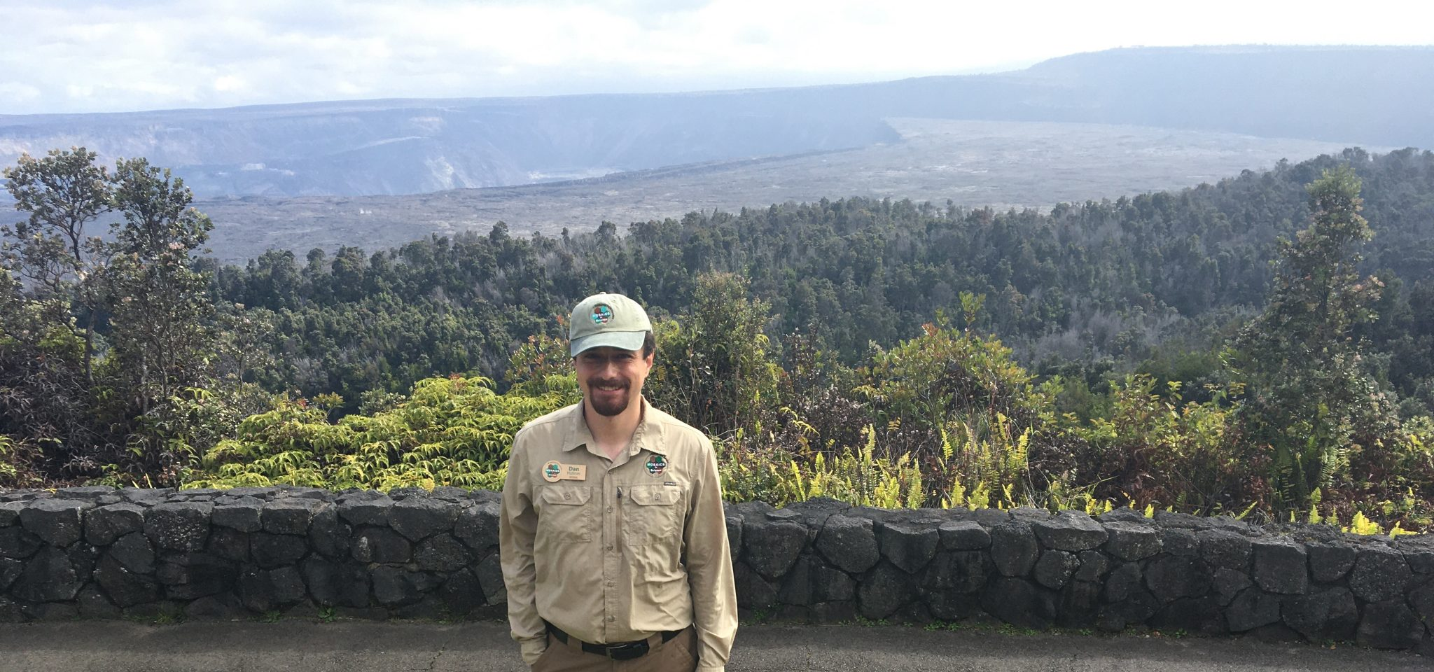 Intern stands in front of large volcanic caldera