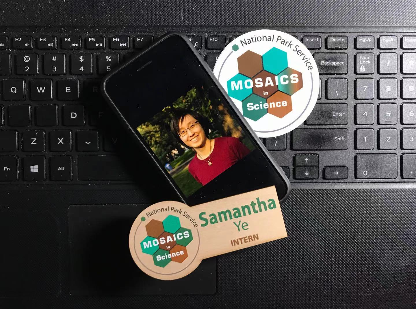 Phone, MIS sticker and name tage for Samantha Ye on top of a laptop keyboard